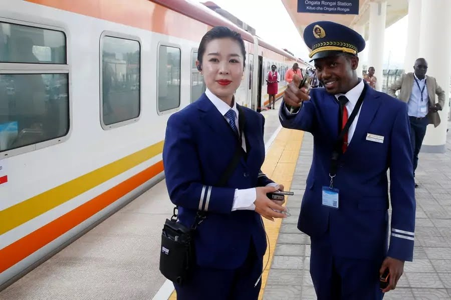 Kenya Railways attendants talk next to a train along the Standard Gauge Railway (SGR) line constructed by the China Road and Bridge Corporation (CRBC) and financed by the Chinese government in Ongata Rongai, Kenya, on October 16, 2019.